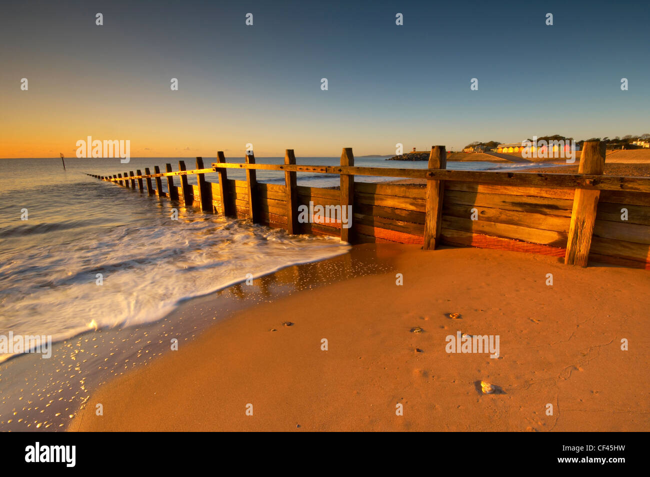 Waves rushing in around wooden sea defences on the Dawlish seafront at dawn. - Stock Image