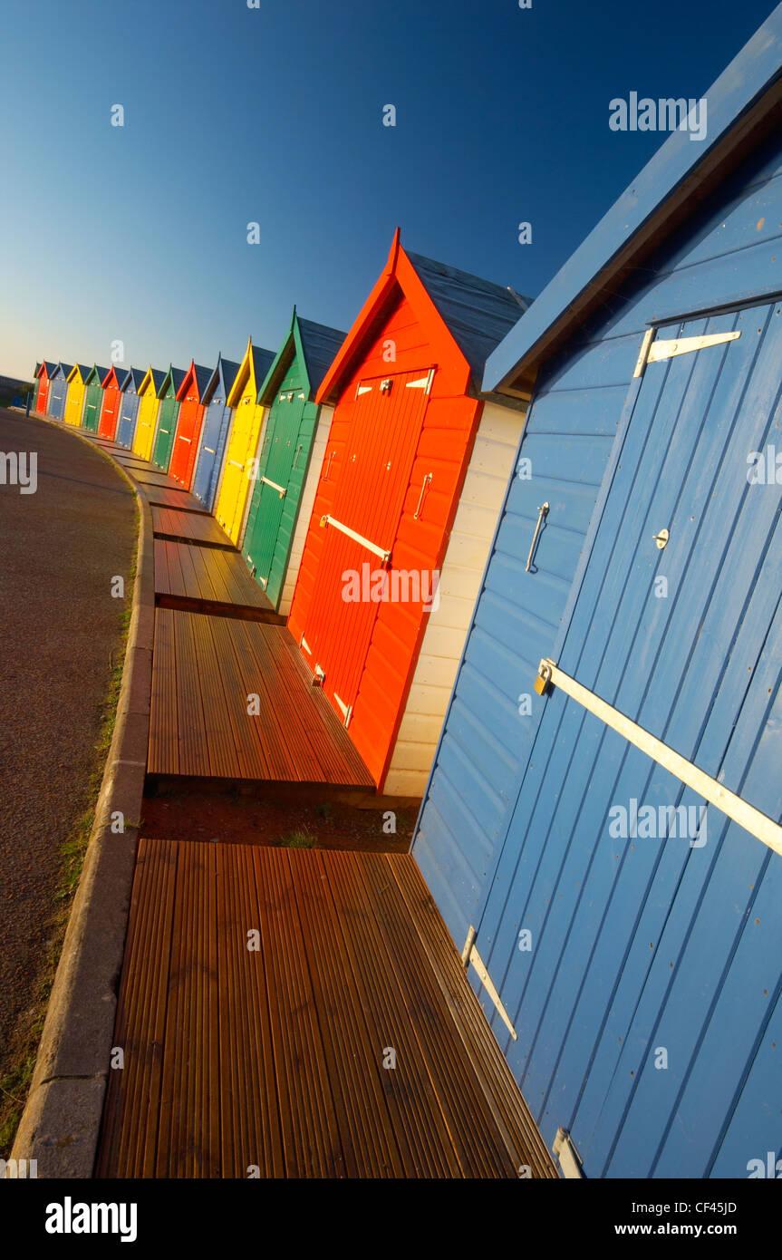 Bright multi coloured beach huts along Dawlish seafront at dawn. - Stock Image