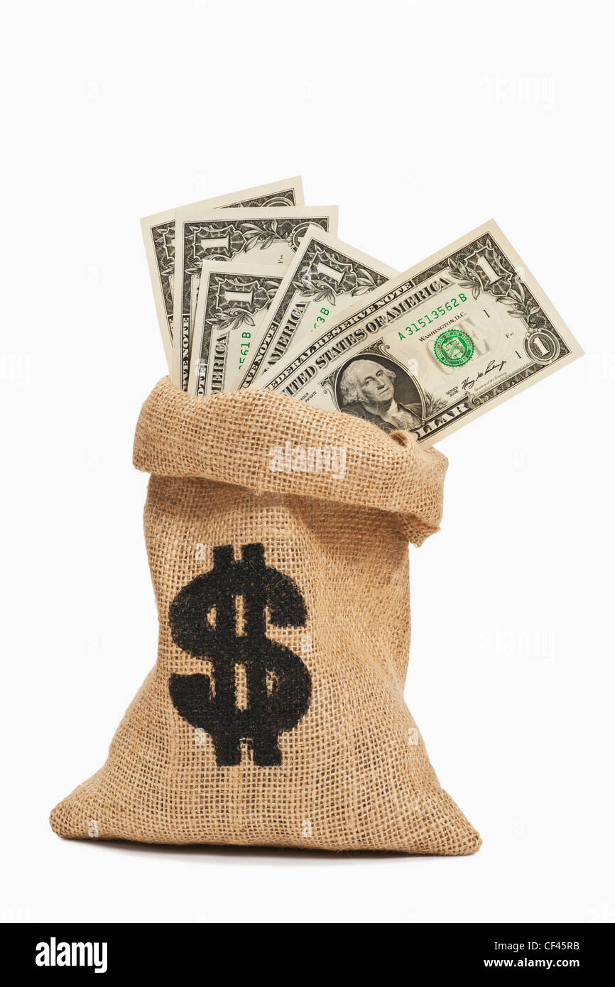 Many U.S.Dollar bills with the portrait of George Washington are in a jute bag. - Stock Image