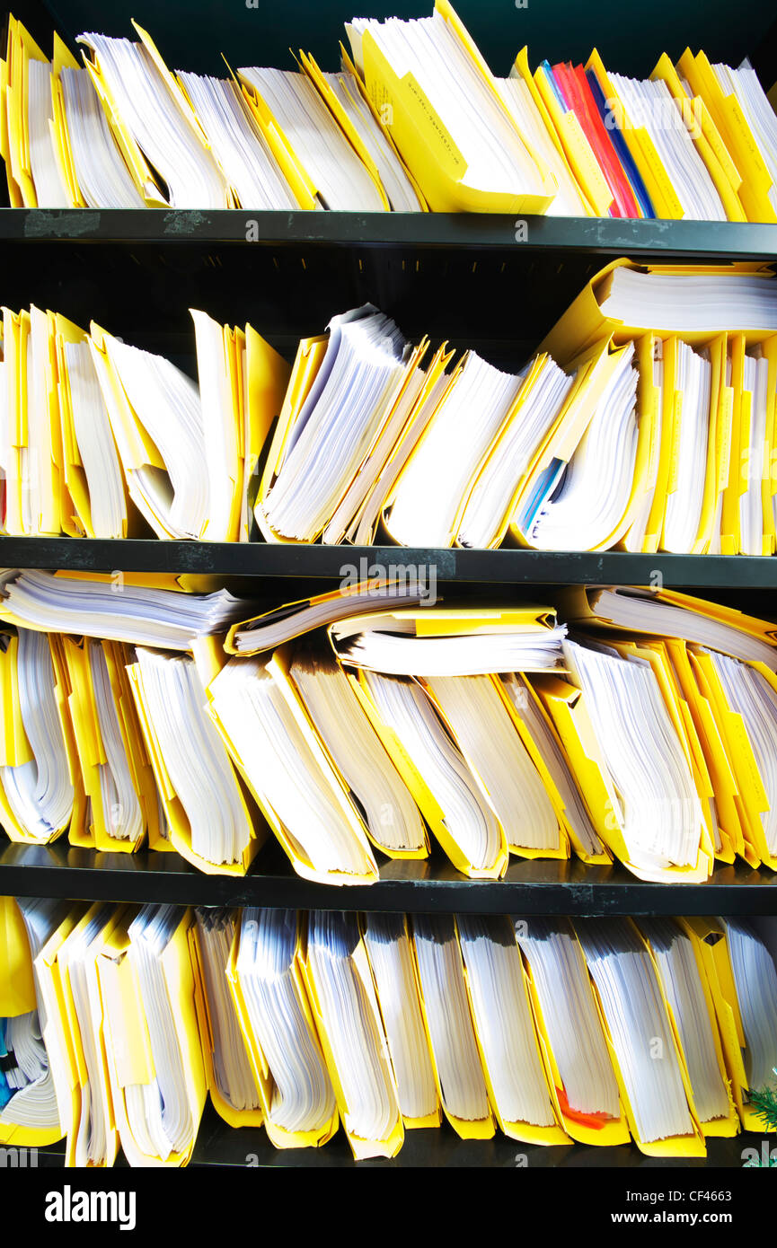 stacks of paperwork and files on shelves in a UK office - Stock Image