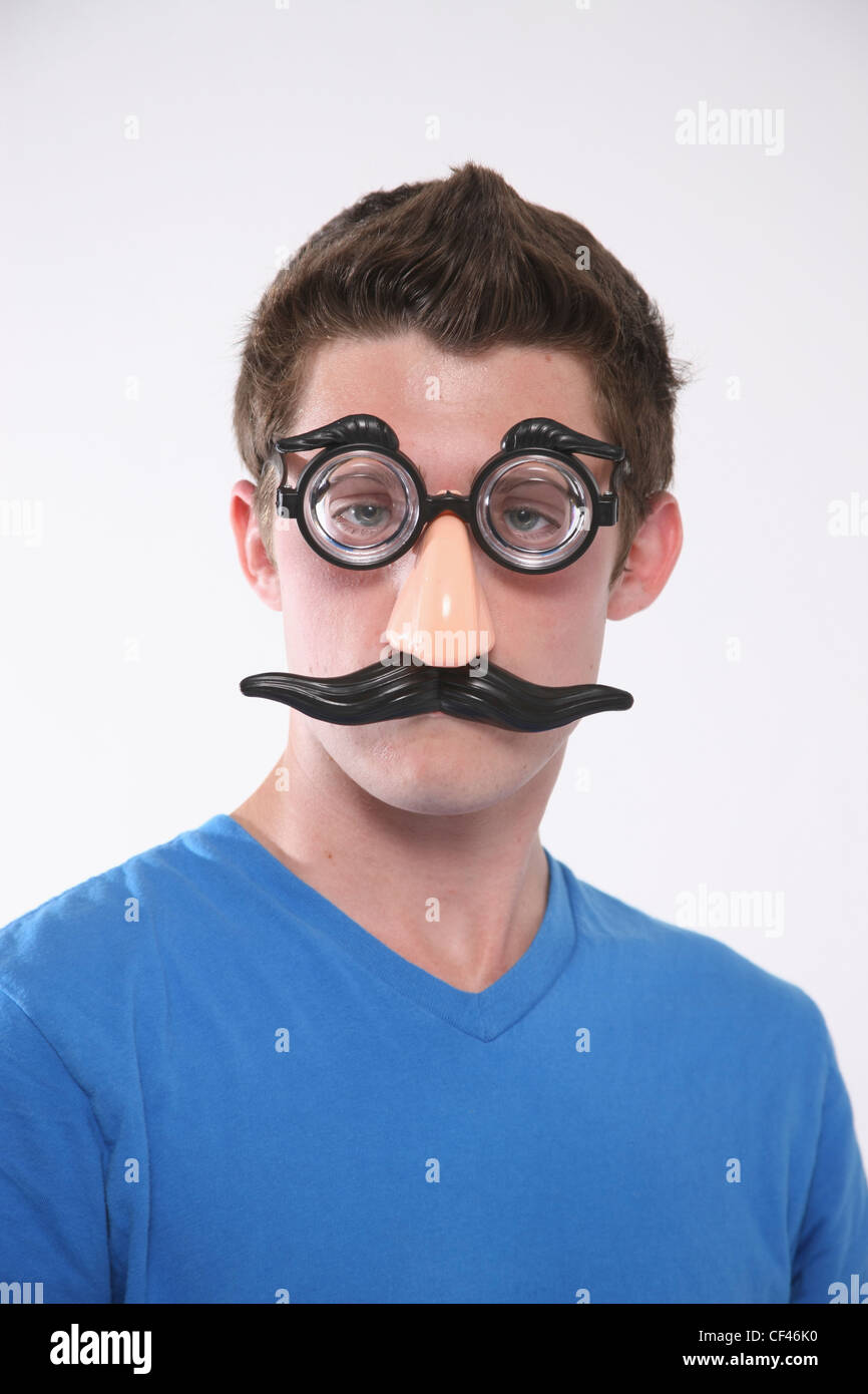 A Teenage Boy Wearing A Groucho Marx Mask; Troutdale Oregon United States Of America - Stock Image