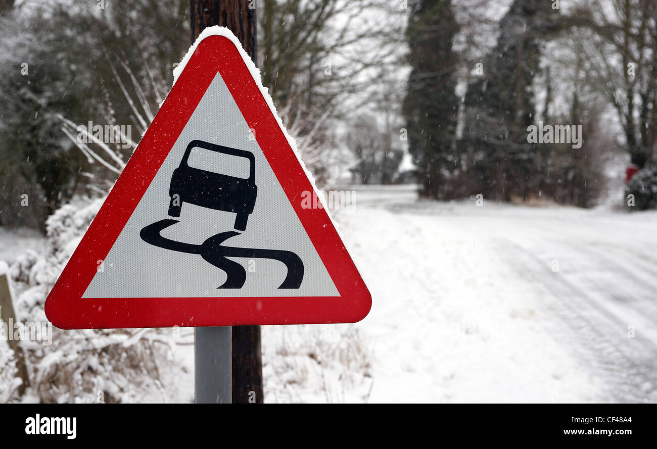 A rural slippery road sign with a snow covered road in the background in Essex. Stock Photo