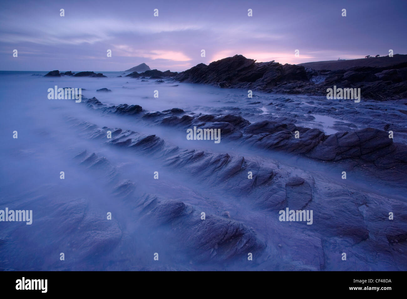 Waves rushing in over rocks on the foreshore at Wembury Bay. - Stock Image