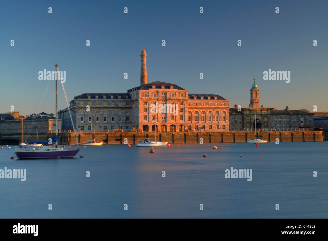 Low evening sunlight illuminating the facade of the Royal William Yard building in Plymouth. - Stock Image