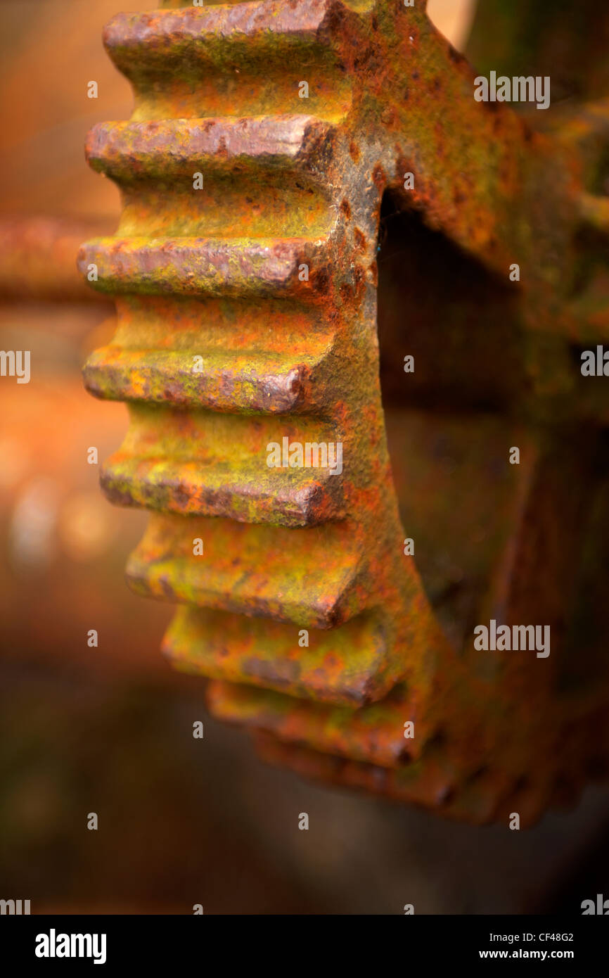 Rusty old iron cog wheel on an old fishing boat pulley system in the Cornish harbour of Cadgwith Cove. - Stock Image