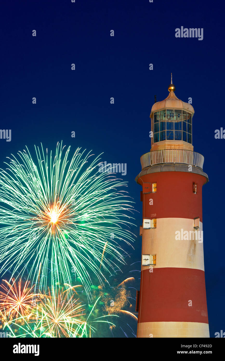 Fireworks exploding in the sky behind Smeaton's Tower over Mountbatten bay and Plymouth Sound at the National - Stock Image