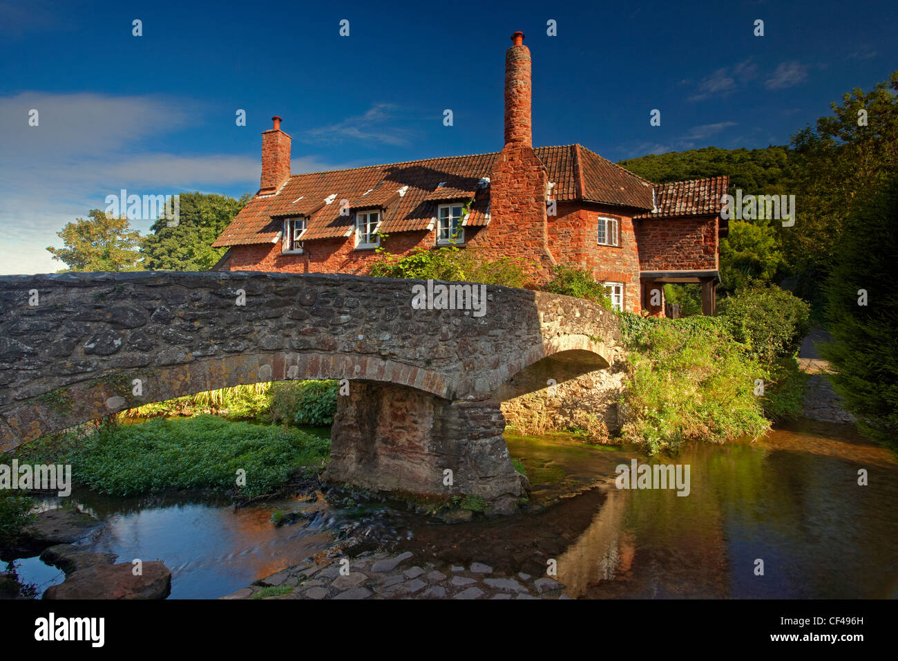 Red sandstone packhorse bridge over the River Aller by a pretty cottage on Exmoor. - Stock Image