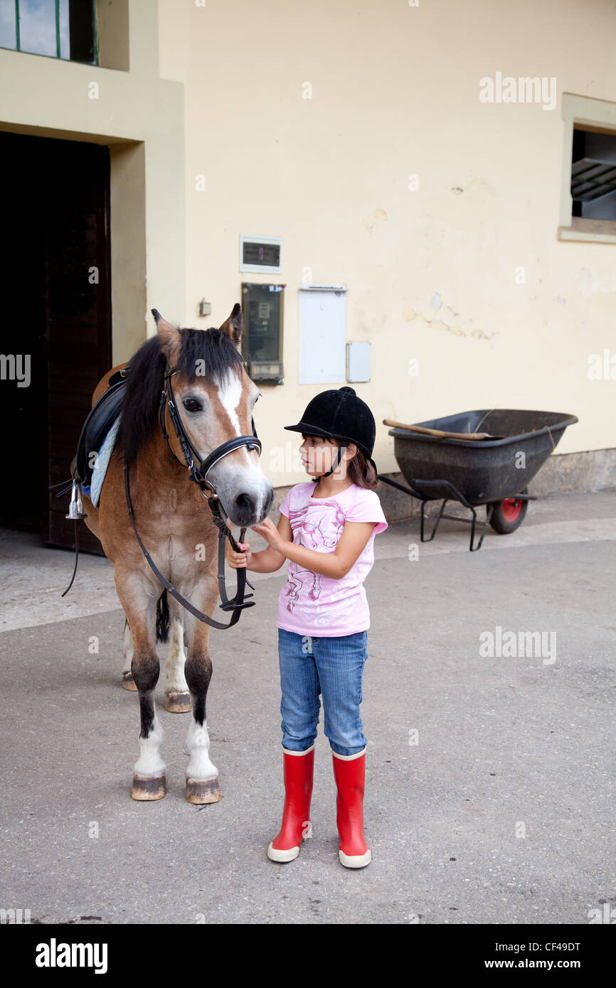 Little girl standing next to her horse ready for a horseback riding lesson. Stock Photo