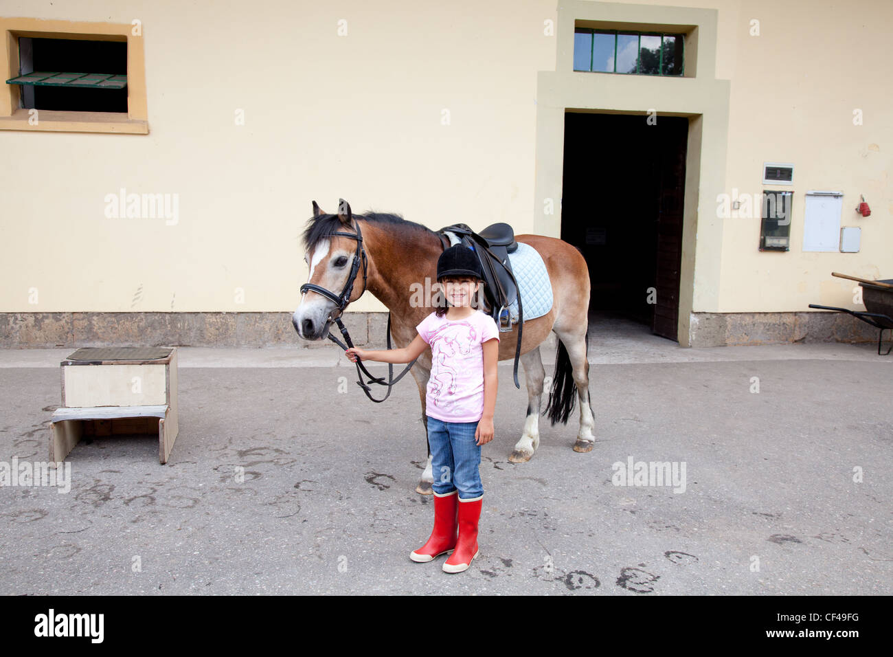 Little girl standing next to her horse ready for a horseback riding lesson. - Stock Image
