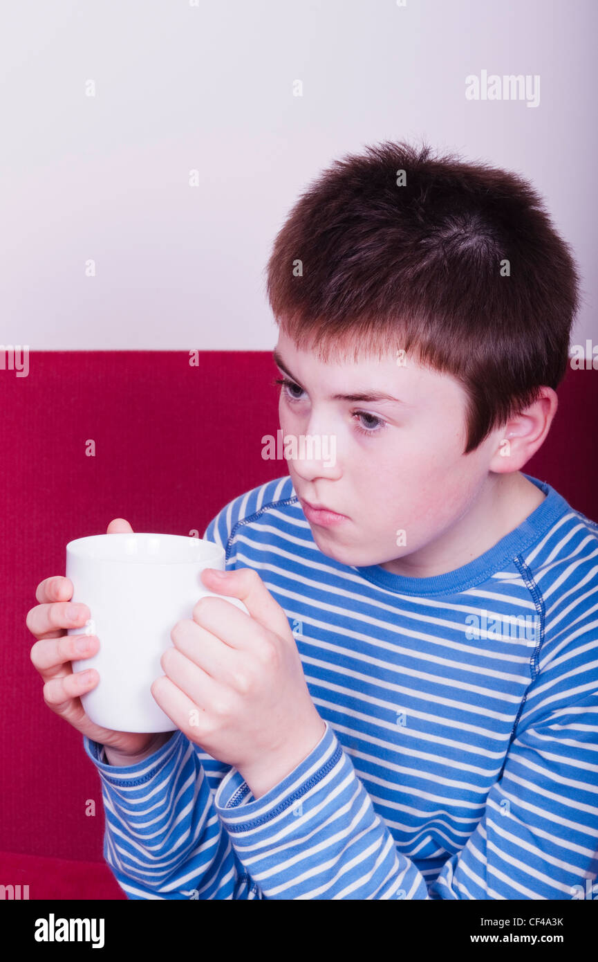 A 12 year old boy watching tv with hot drink in England , Britain , Uk