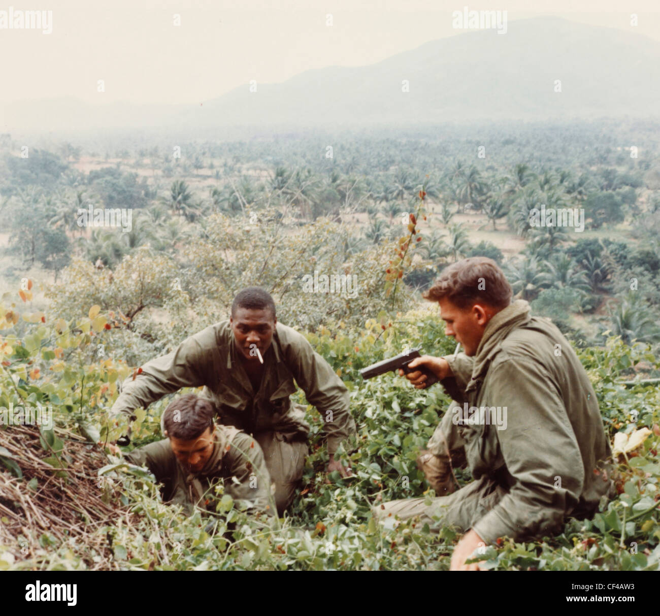 riflemen of 8th Cavalry, 1st Cavalry Division enter a cave on mount in search for Viet Cong and contraband during - Stock Image