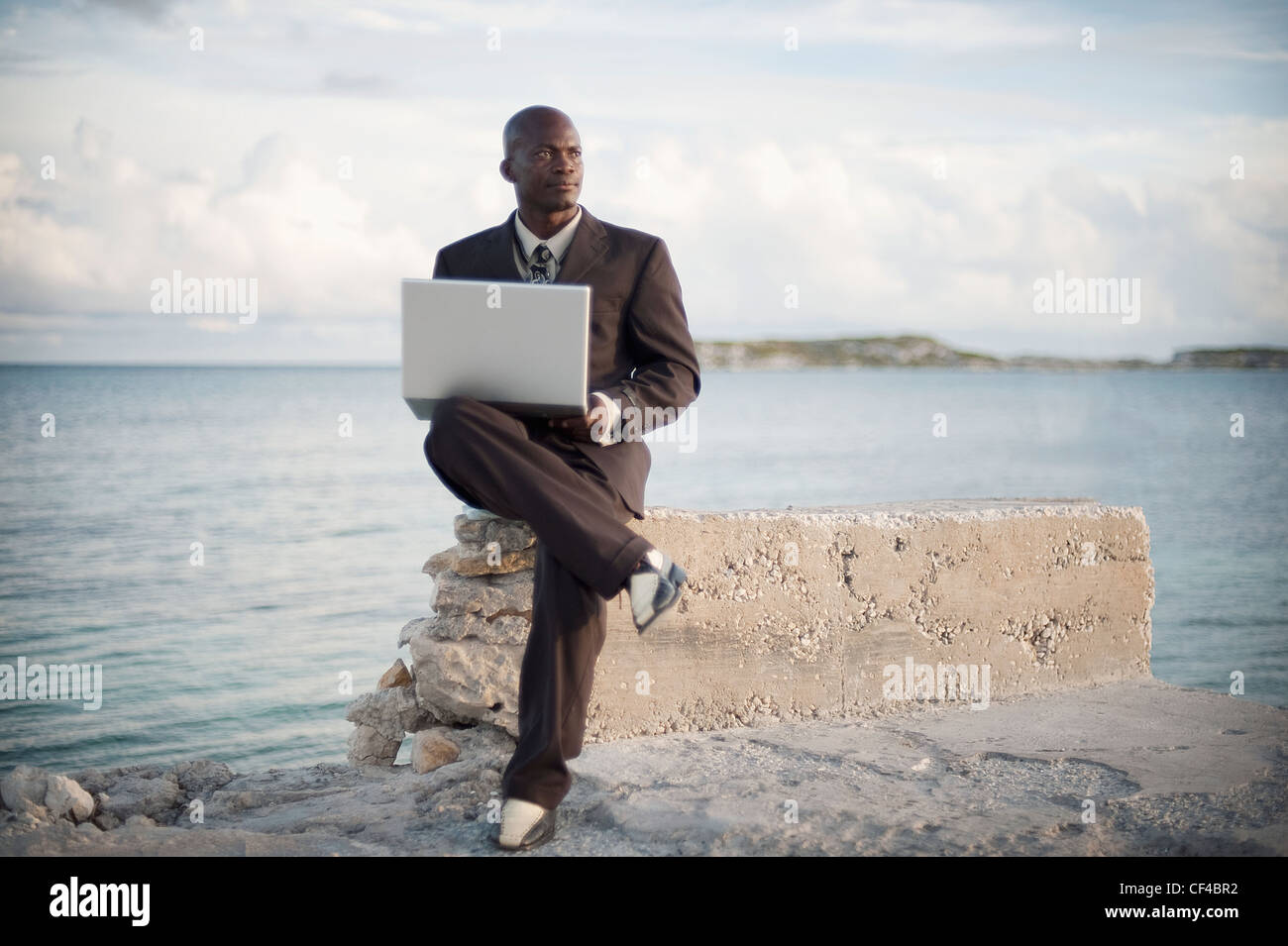A Businessman With A Laptop Computer Sitting On A Rock Ledge At The Edge Of The Water; South Caicos Turks And Caicos - Stock Image