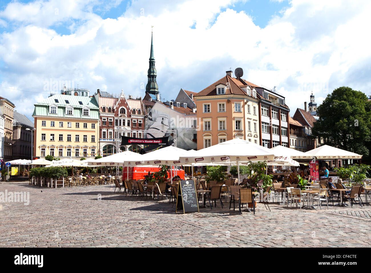 Outdoor cafes in Dome Square in old town Riga with the spire of St. Peter's Church in background. - Stock Image