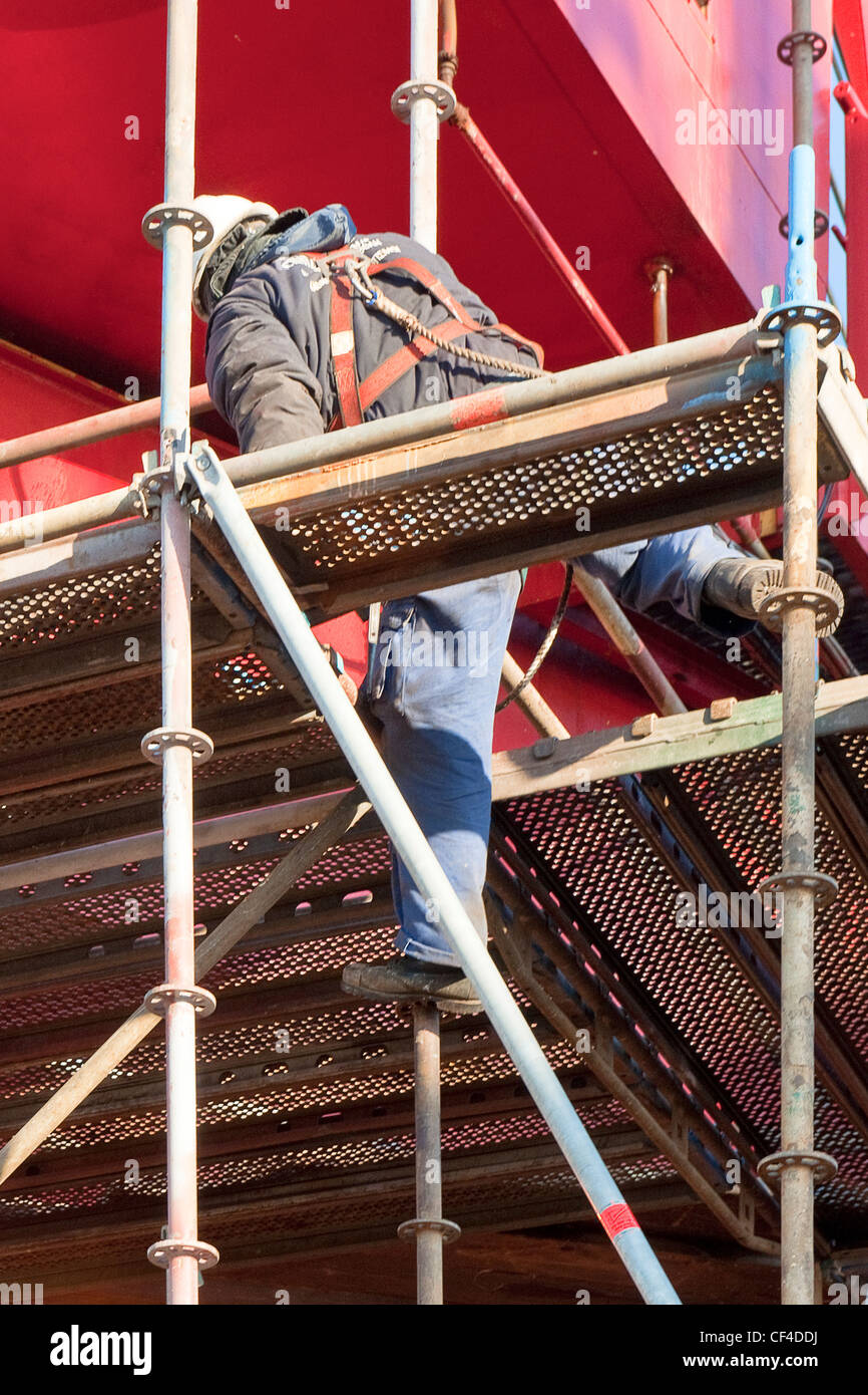 Scaffolder, wearing a safety harness, climbing up an unfinished scaffold around a huge, industrial structure - Stock Image