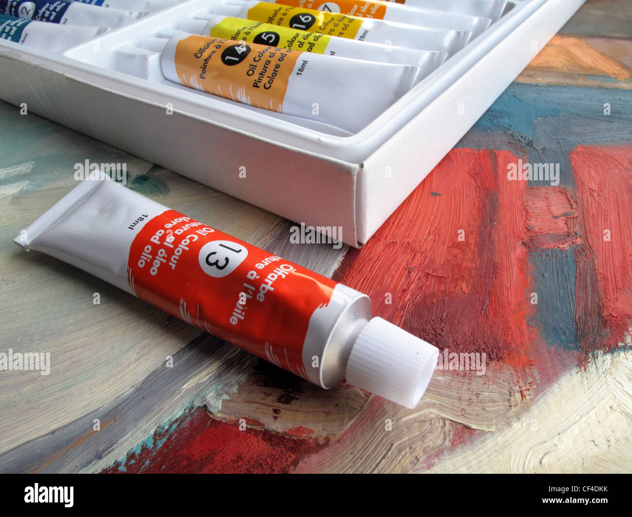 A new tube of red oil paint sits next to a box of oil paints -  all lie  on top of an oil painting. - Stock Image