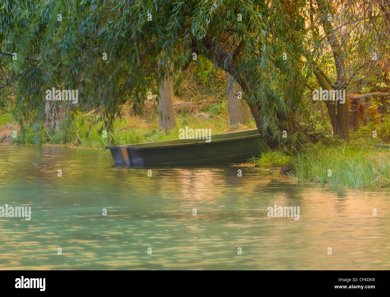 Rowing boat moored on bank of Lago del Espejo, Mirror Lake, at Parque Natural de Monasterio de Piedra, Spain - Stock Image