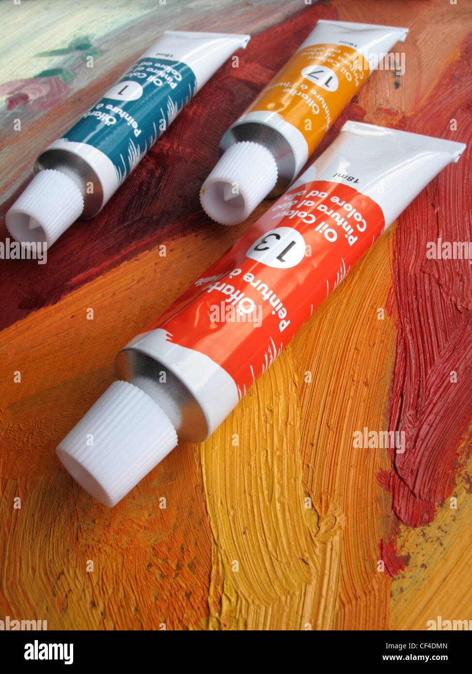 Tubes of red, blue, and yellow oil paint lie on top of an oil painting. - Stock Image