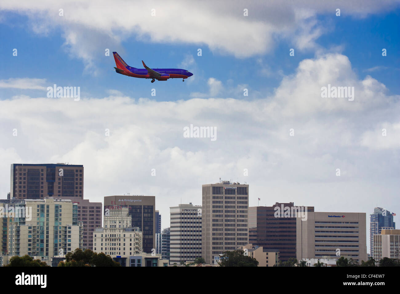 Airliner over San Diego city skyline on final approach to Lindbergh field-San Diego, California, USA. - Stock Image