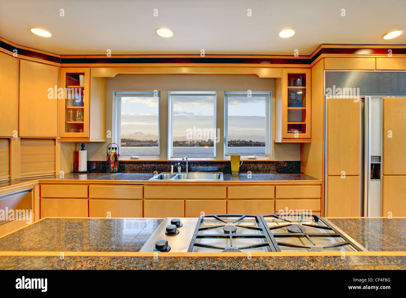 Large Luxury Modern Wood Kitchen With Granite Counter Tops And Yellow  Hardwood Floor.