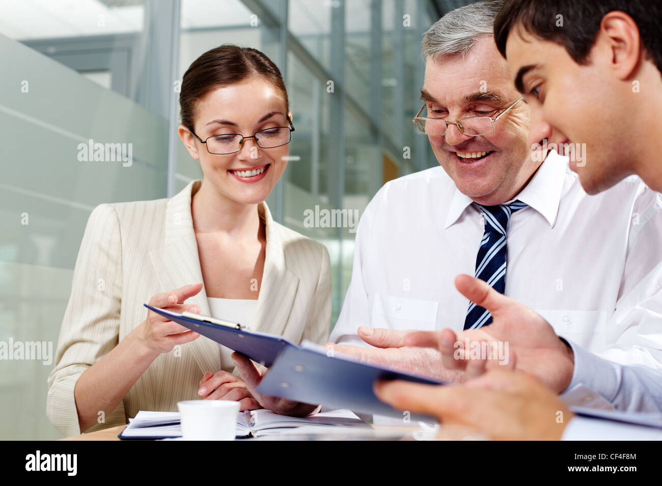 Boss approving a report of his younger subordinates - Stock Image