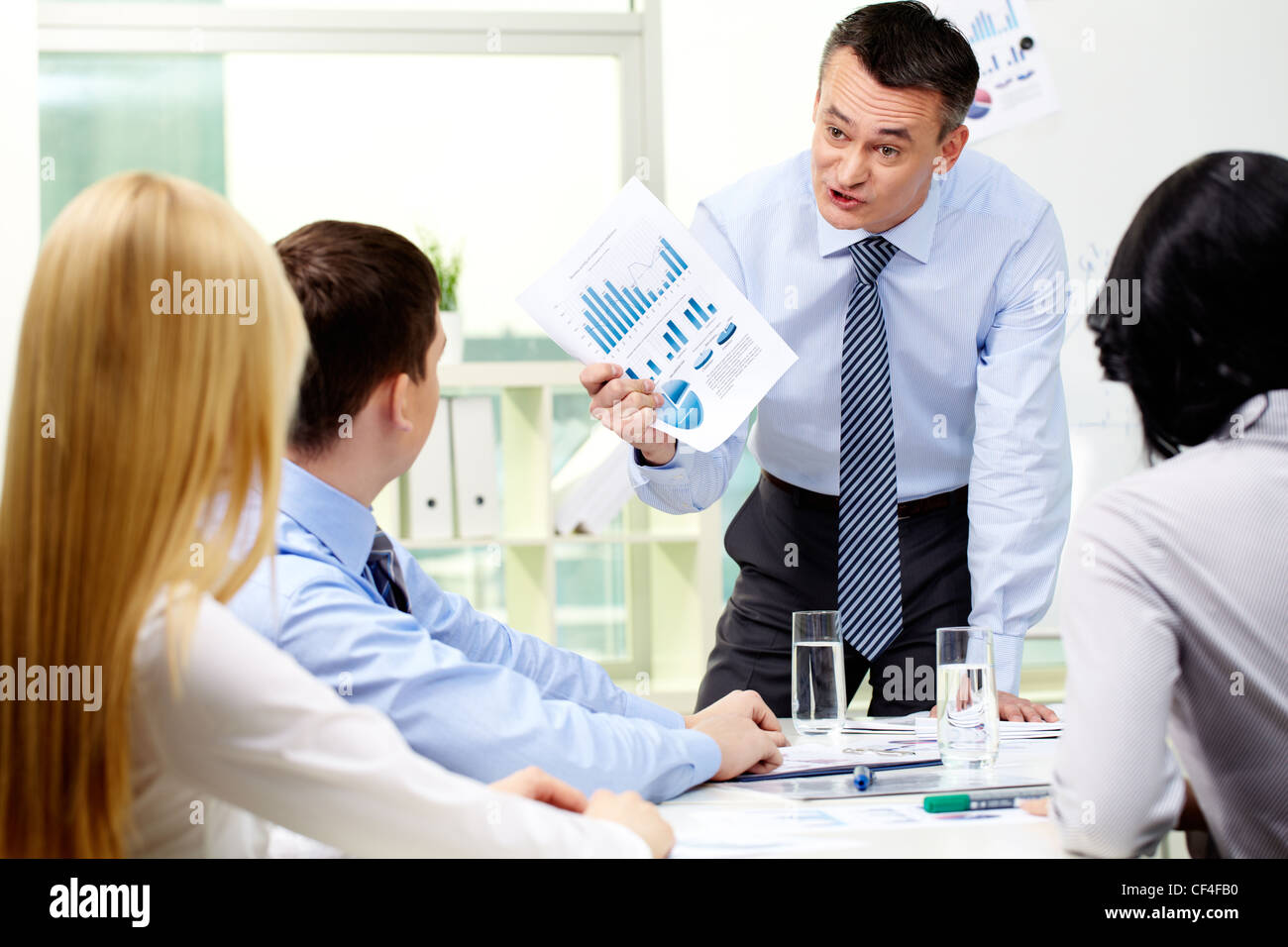 Business worker showing charts and graphs to his employees with a furious look - Stock Image