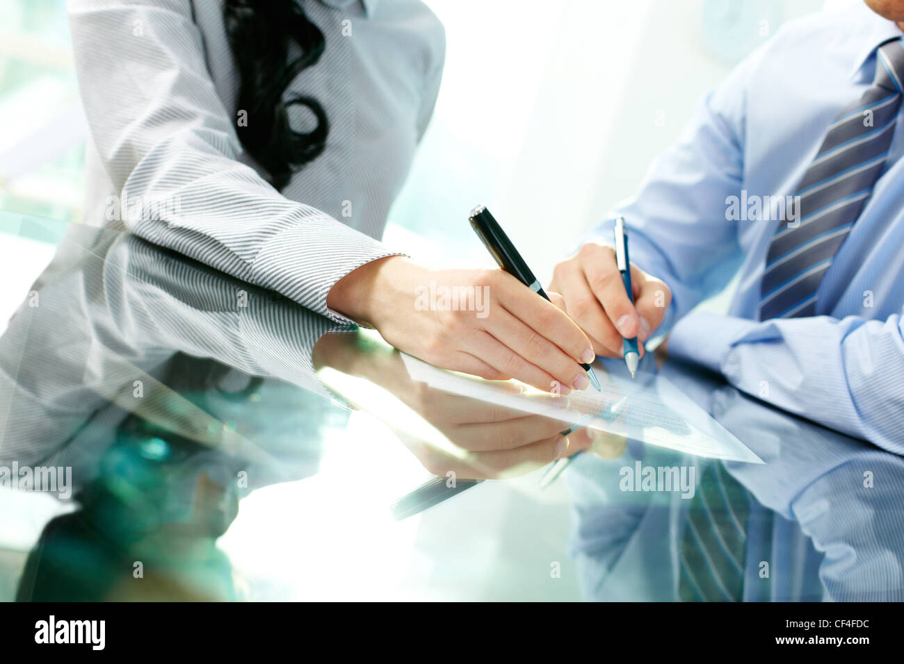 Tilt up of two business partners signing a contract and closing the deal - Stock Image