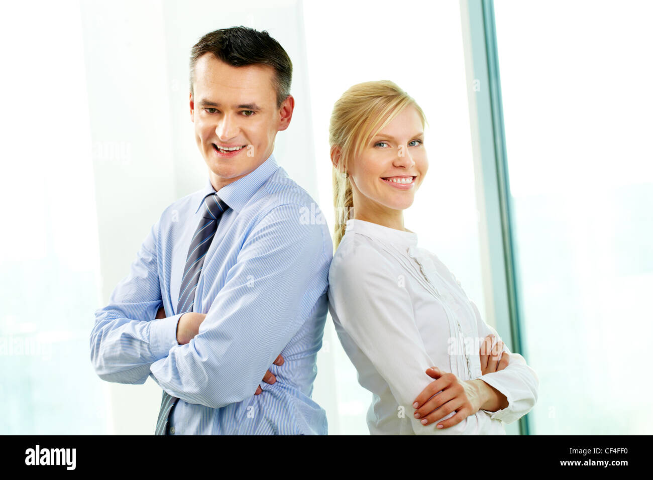 Two confident partners standing back to back and smiling - Stock Image