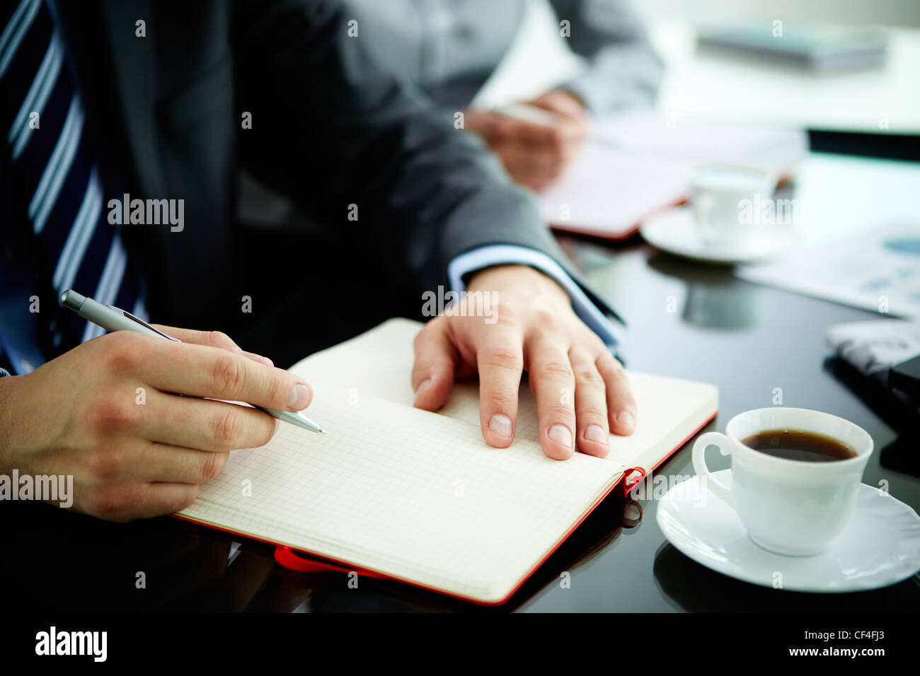 Image of male hand with pen over open notebook during planning work - Stock Image