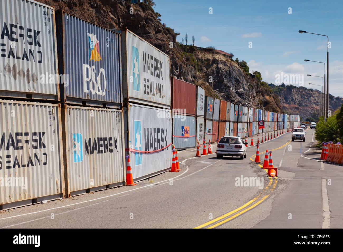 A line of shipping containers protects Main Road in the Christchurch suburb of Sumner from rockfalls - Stock Image