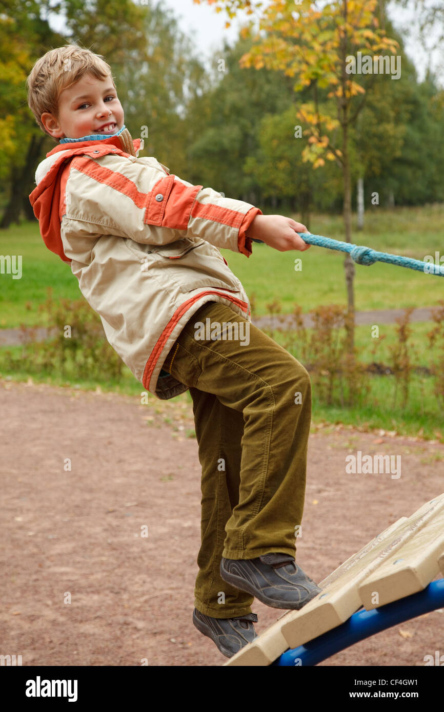 Boy in jacket is on playground in autumn park. Smiling, he climbs the stairs holding onto a rope. - Stock Image