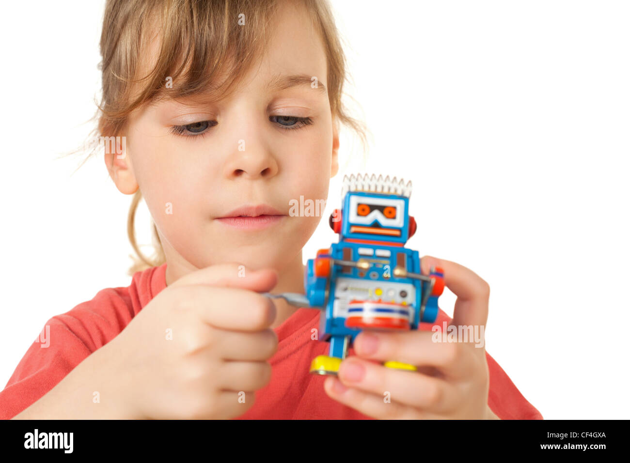 pretty little girl in red T-shirt plays with clockwork robot isolated on white background - Stock Image