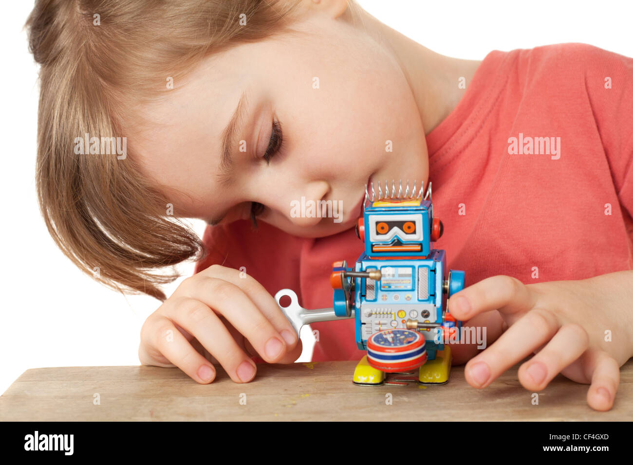 little girl in red T-shirt plays with clockwork robot isolated on white background - Stock Image