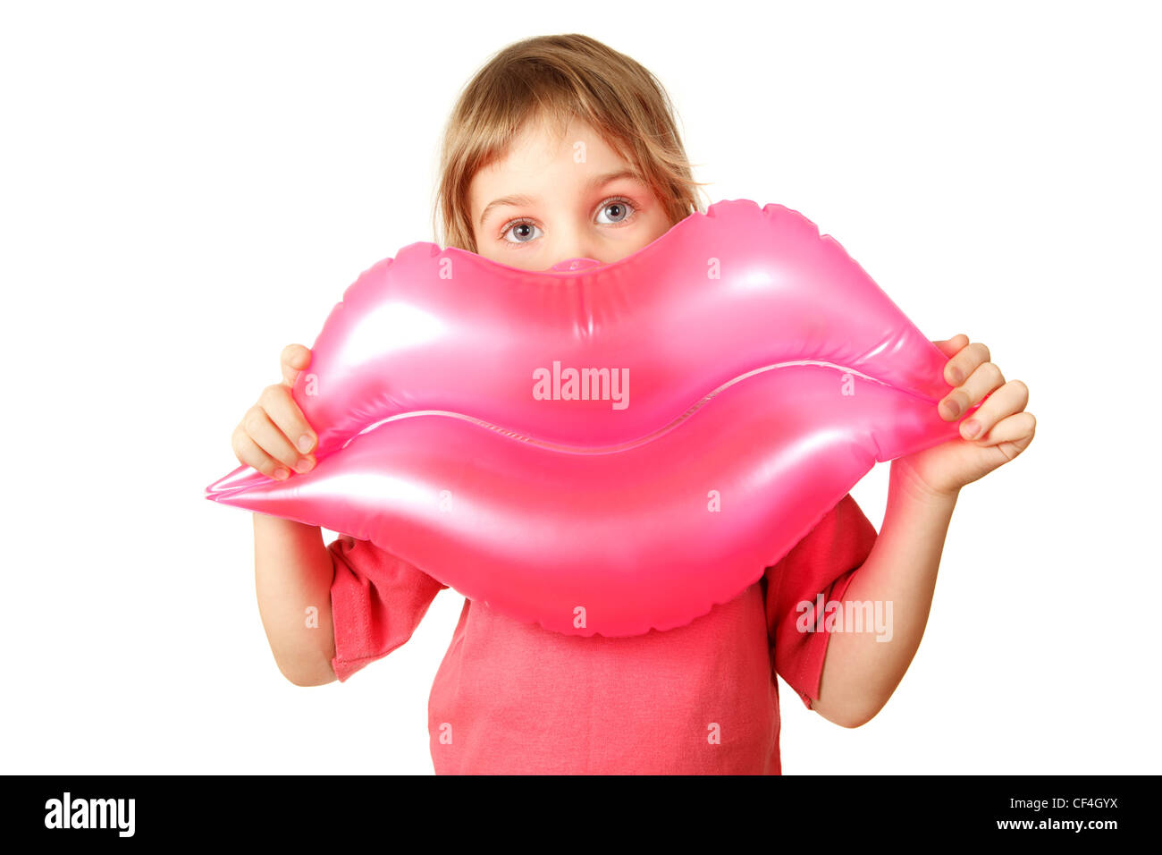 Girl holds toy, inflatable pink lips. Isolated on white background. - Stock Image