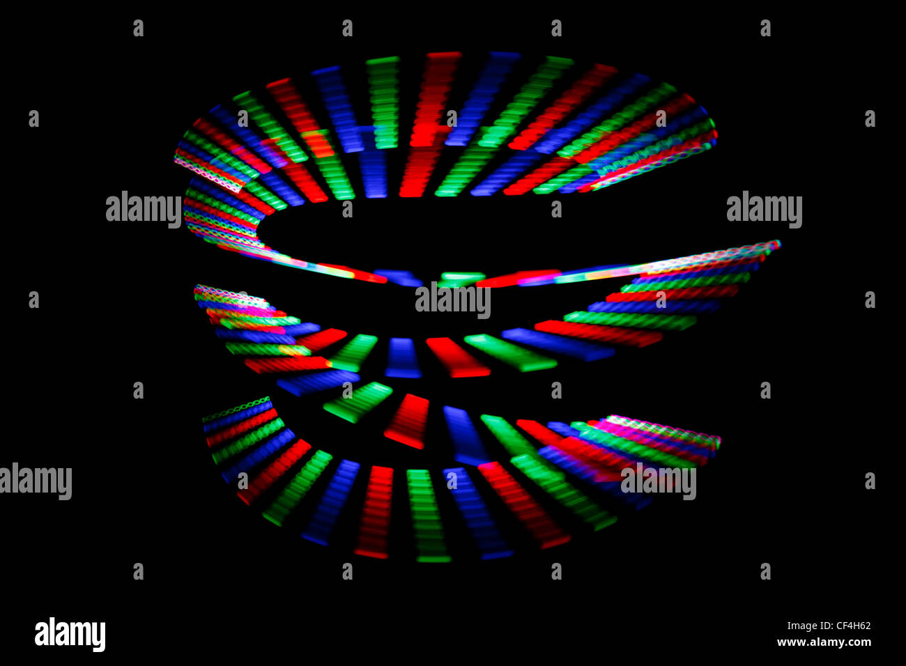 Luminous colors of rainbow trail in form of spiral on black background. Isolated. - Stock Image