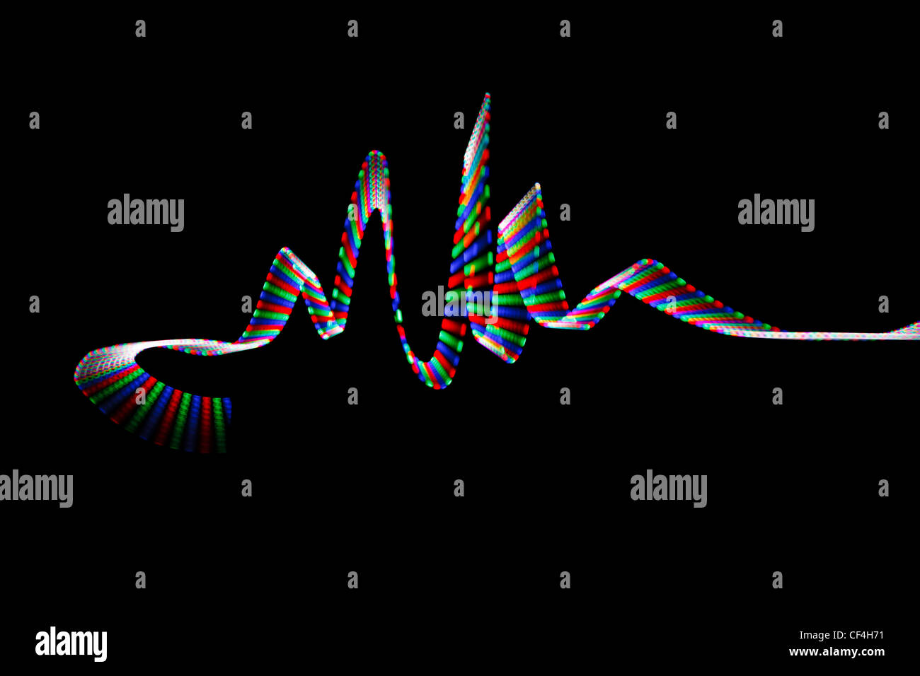 Colorful LED track, in form of waves on black background. - Stock Image