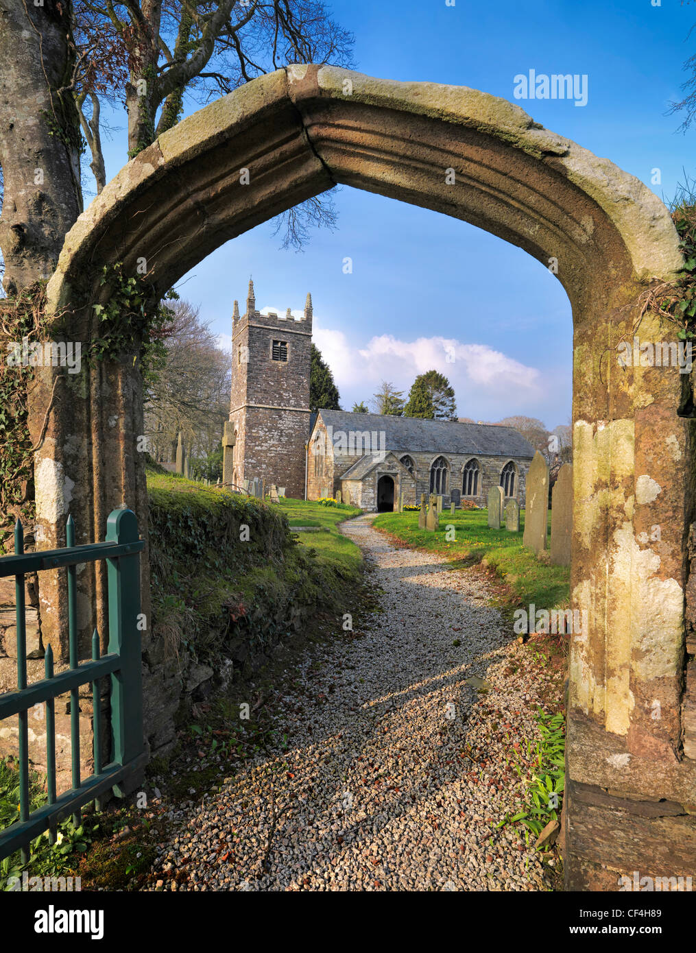 Path leading through the churchyard to Braddock Church, dedicated to St Mary the Virgin. The earliest parts of the - Stock Image