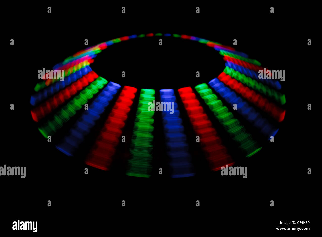 Colorful trace rotating LED in form of a disc on a black background. - Stock Image