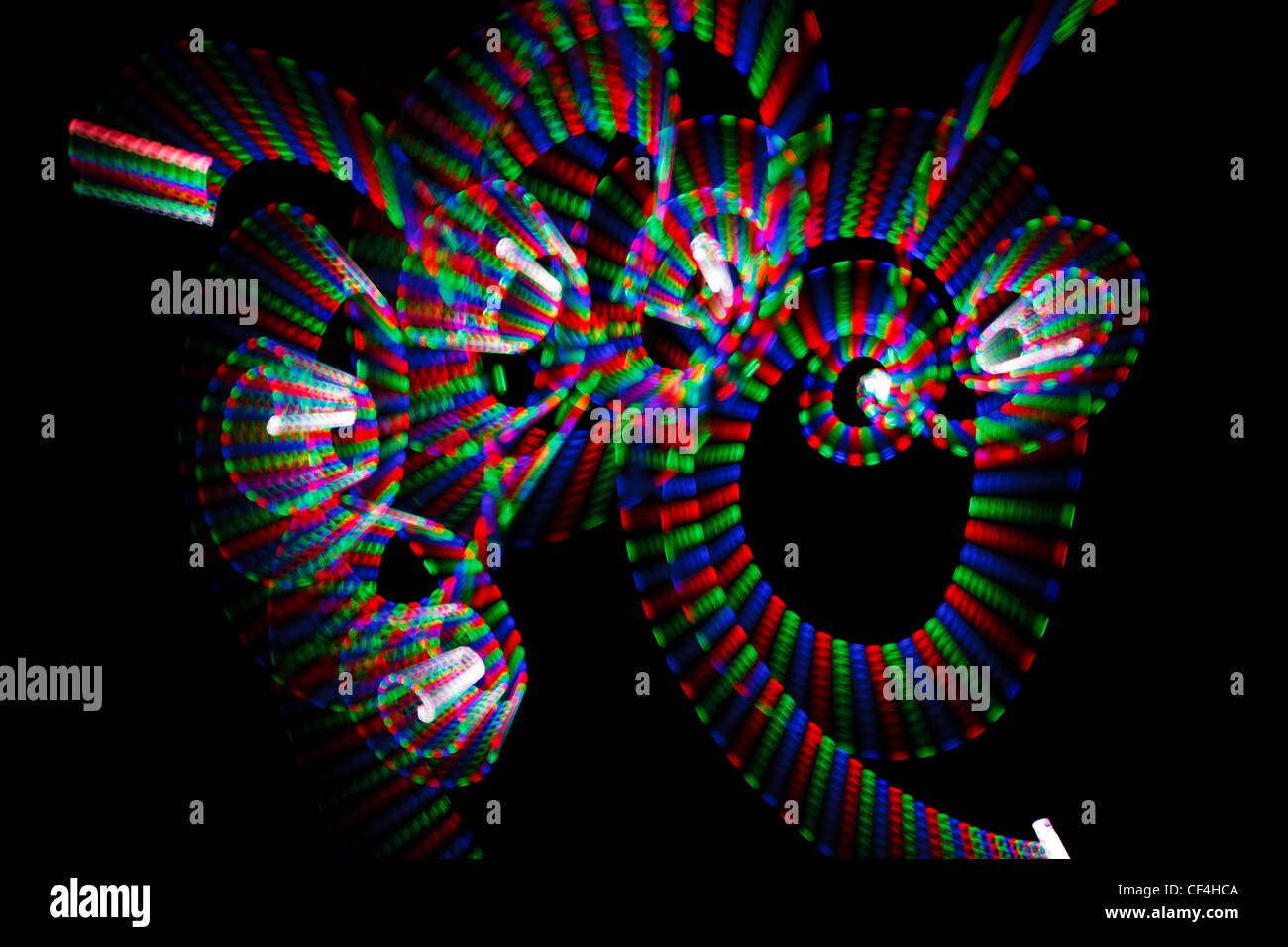 Abstract multicolored freezelight in form of spirals on black background. - Stock Image