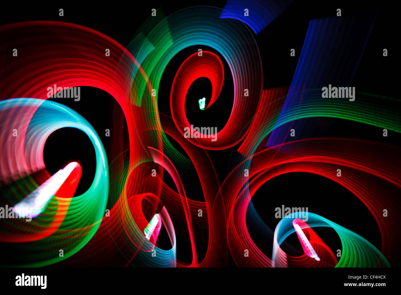 Abstract luminous patterns in form of spirals on black background. - Stock Image
