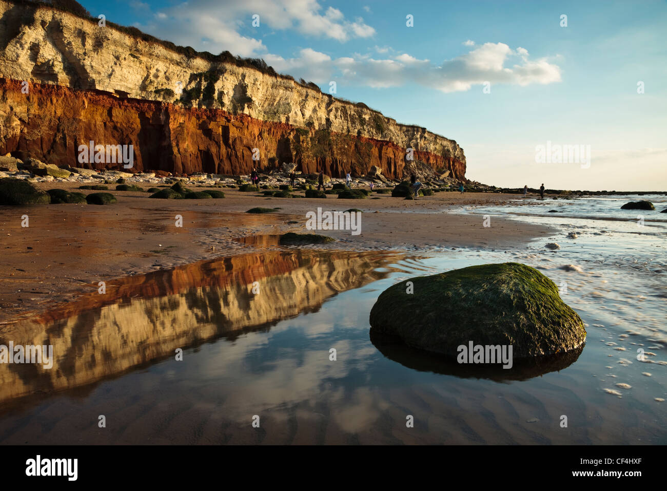 The two tone cliffs at Hunstanton reflected in a pool of water on the beach. - Stock Image