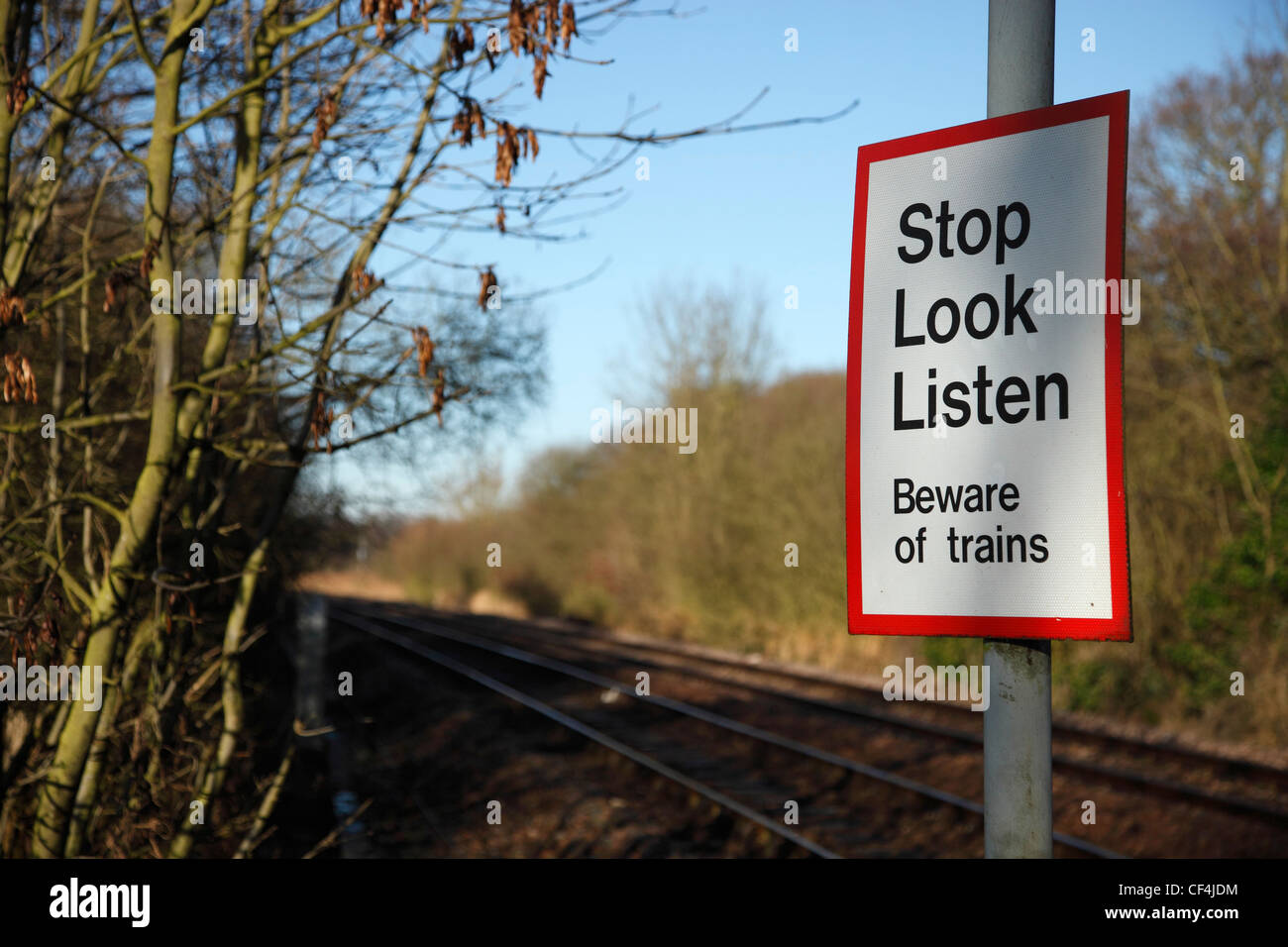 A beware of trains sign by the side of the railway line with a speeding train approaching In Norwich. - Stock Image