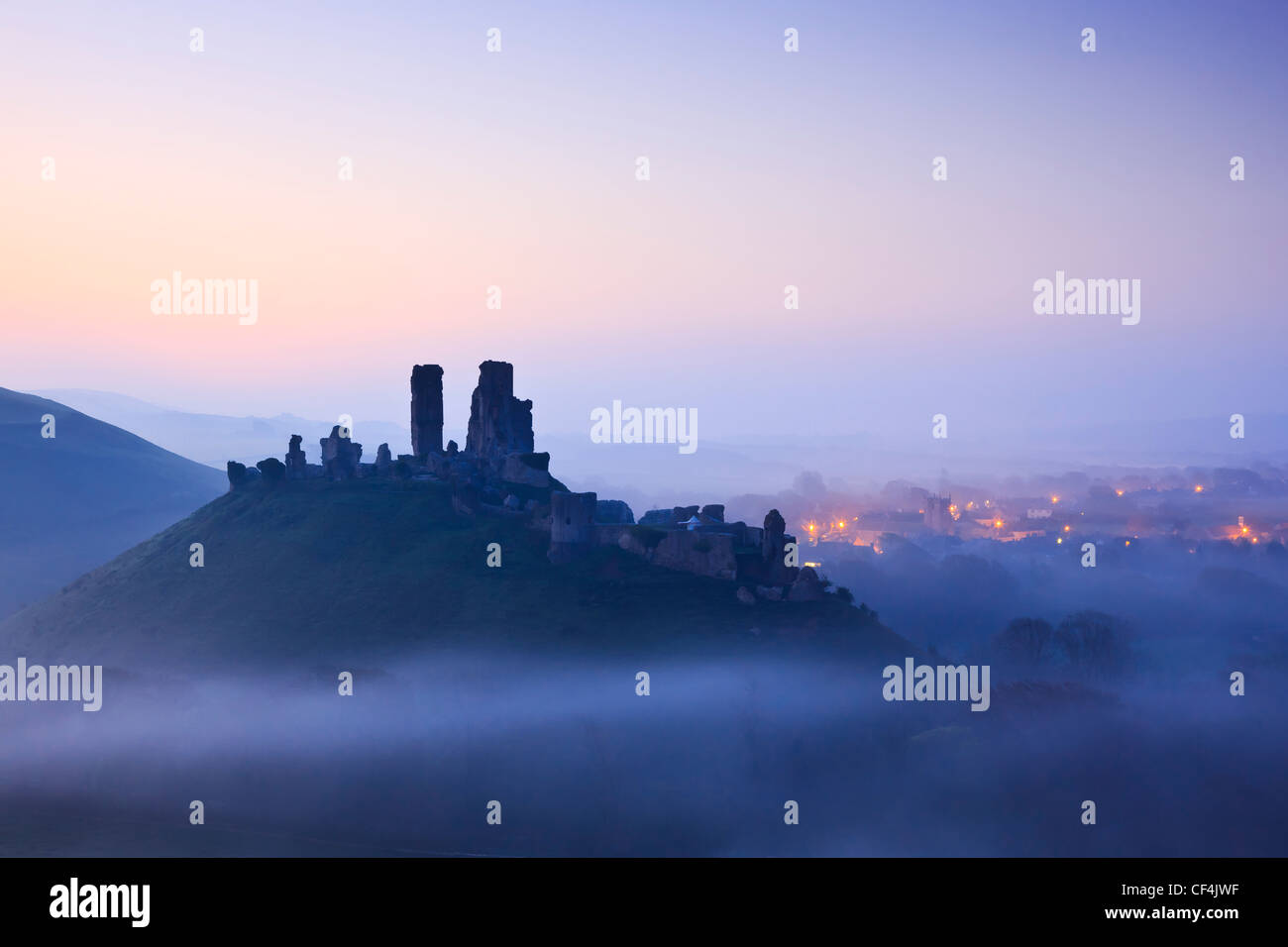 Corfe Castle, dating back to the 11th century, rising above pre-dawn mist. - Stock Image