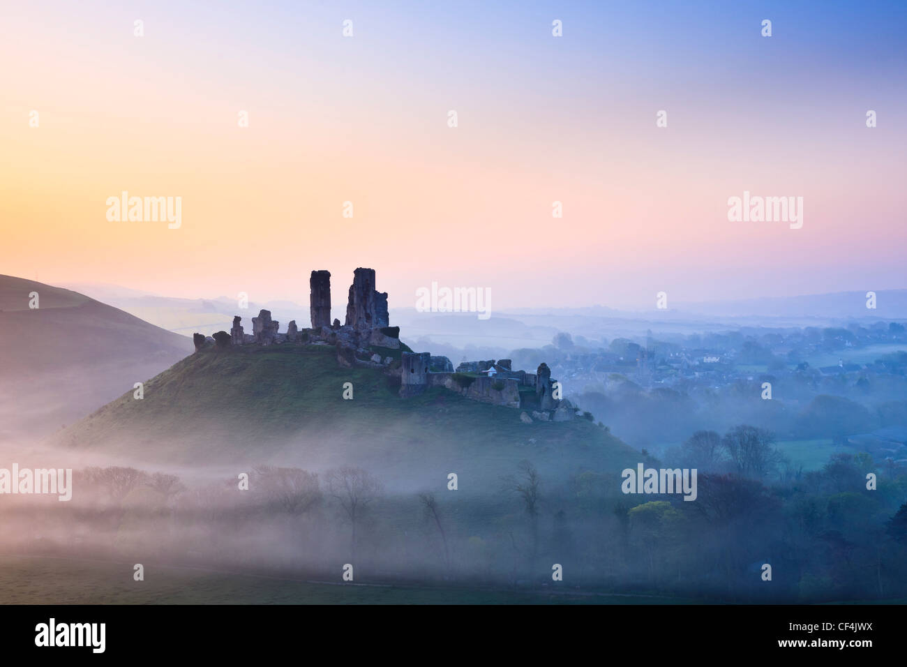 Corfe Castle, dating back to the 11th century, shrouded in mist at sunrise. Stock Photo