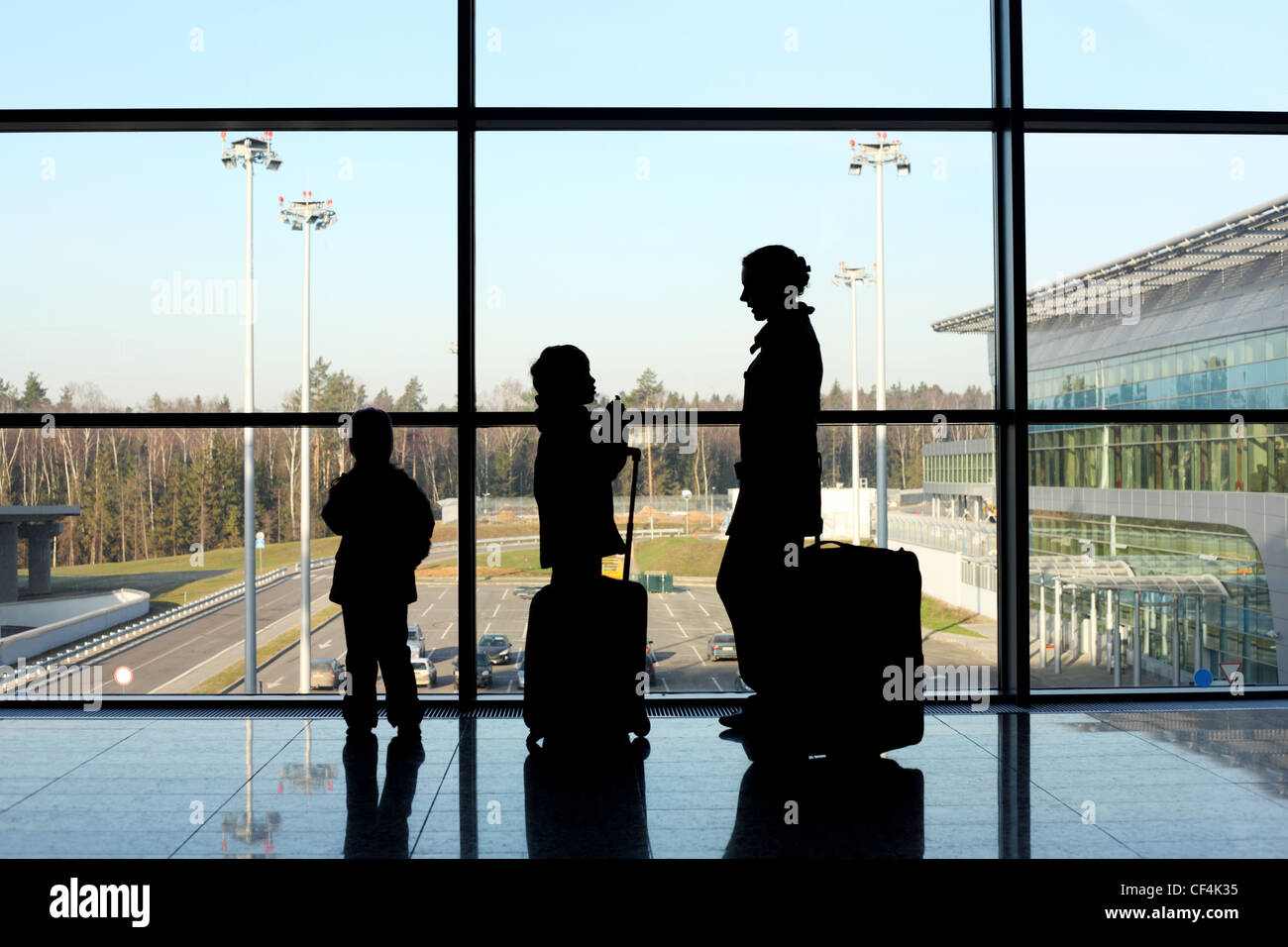 silhouette of mother, son and daughter with luggage standing near window in airport - Stock Image