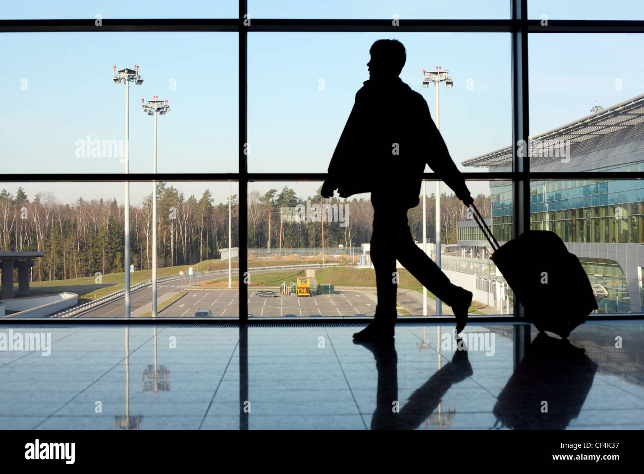 silhouette of man with luggage walking left near window in airport focus on street Stock Photo