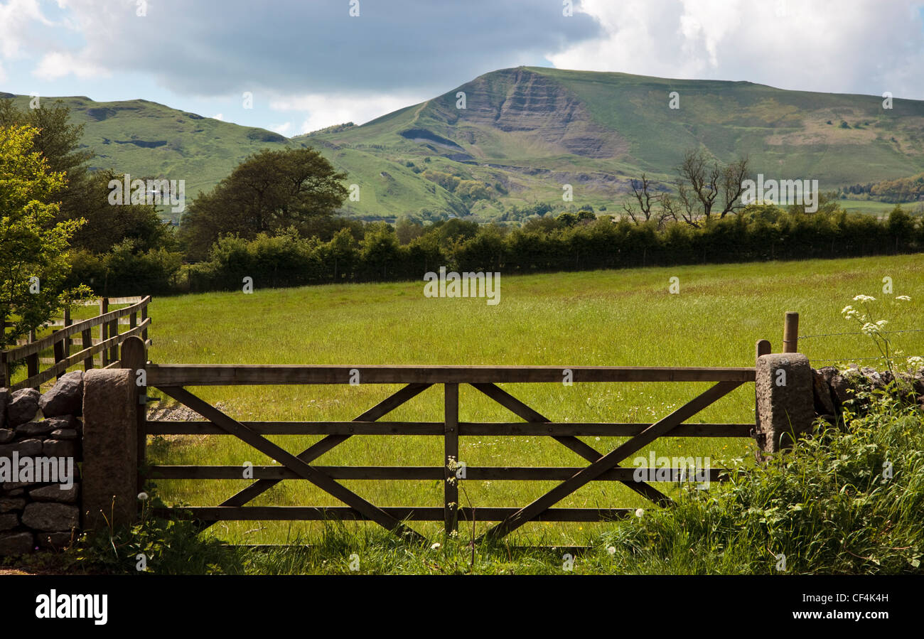 View across a field over a farm gate towards Mam Tor, a hill in the High Peak of Derbyshire, also known as the Shivering - Stock Image