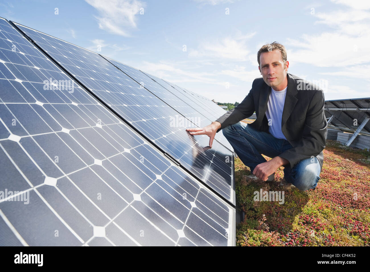 Germany, Munich, Man touching solar panel in solar plant, smiling, portrait - Stock Image