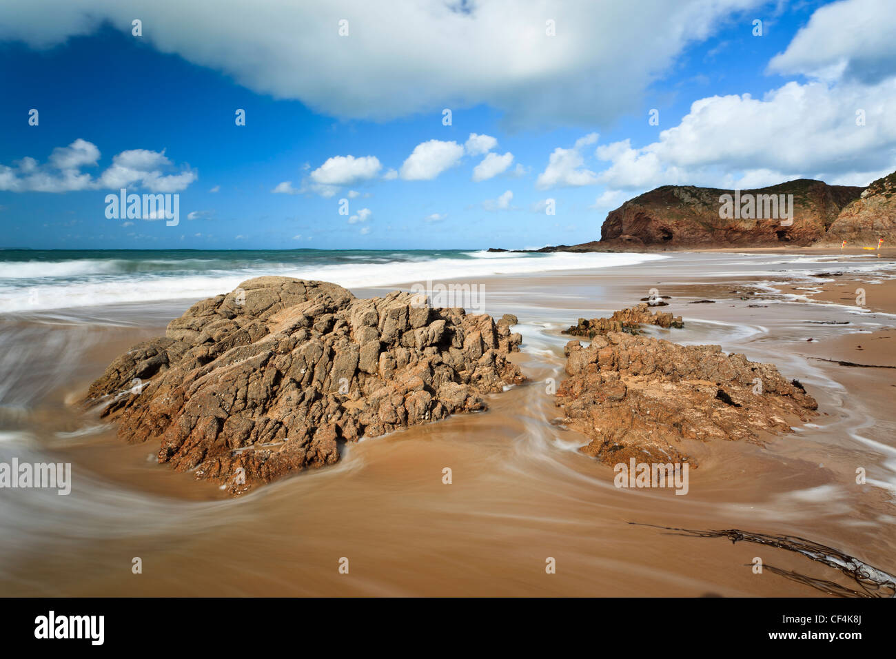 Swirling tide around rocks on the sandy beach at Plemont Bay in Jersey. - Stock Image