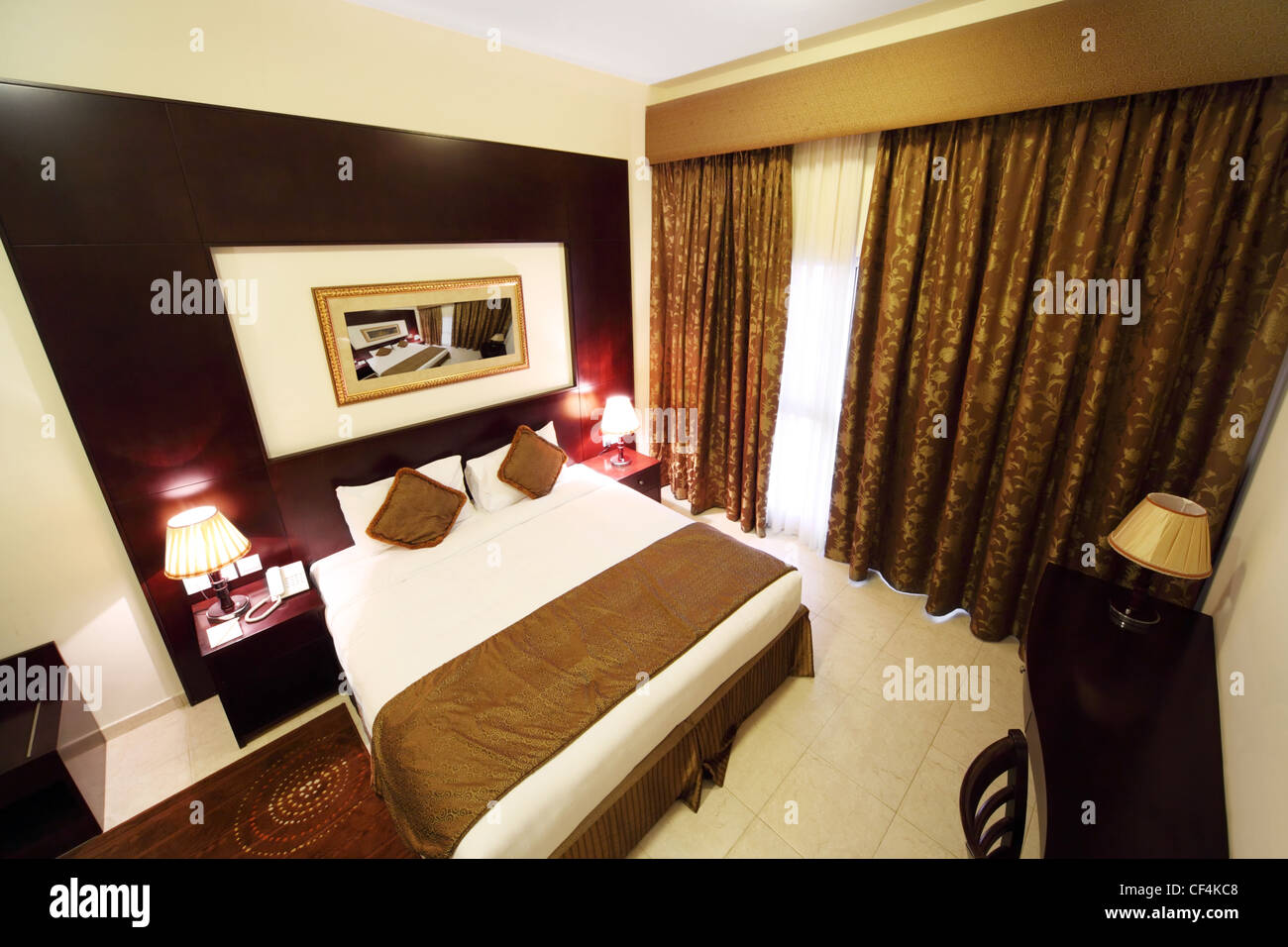 Bedroom With White Walls Brown Curtain And Big Double Bed View From