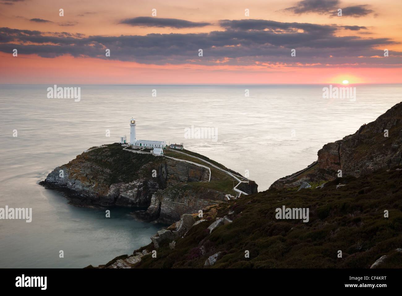 The sun setting on the horizon behind South Stack Lighthouse, a spectacular lighthouse just off Holy Island on the Stock Photo
